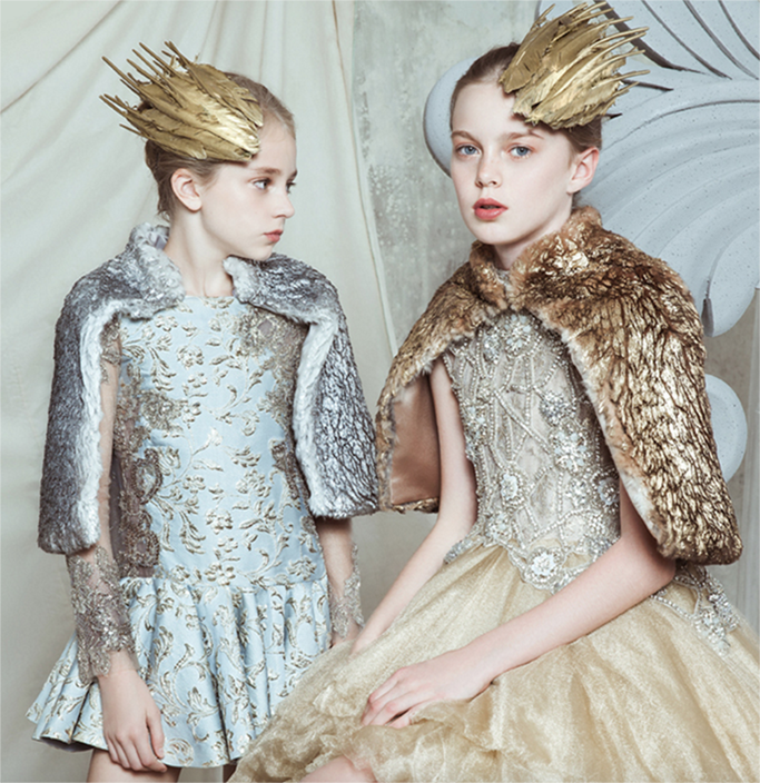 Two girls sat in dresses with gold feather crowns